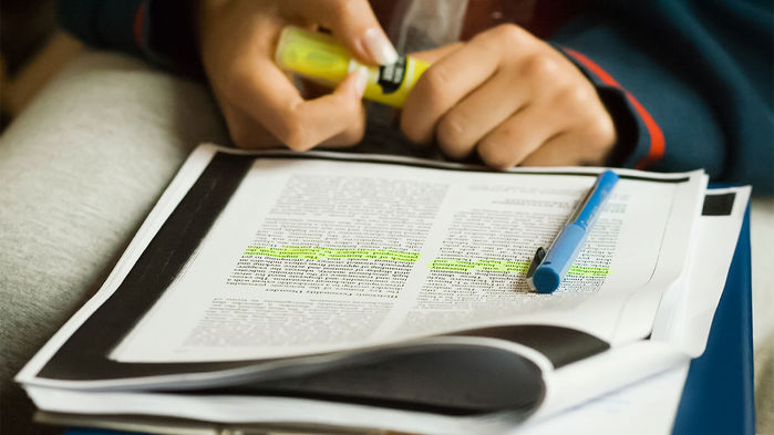 person reading and highlighting a scientific paper